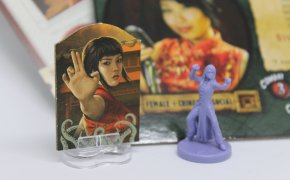 Standee di Eldritch Horror a sinistra e miniatura di Fortune and Glory: the Cliffhanger Game a destra.
