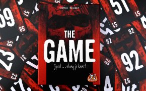 The game: copertuna su sfondo di carte